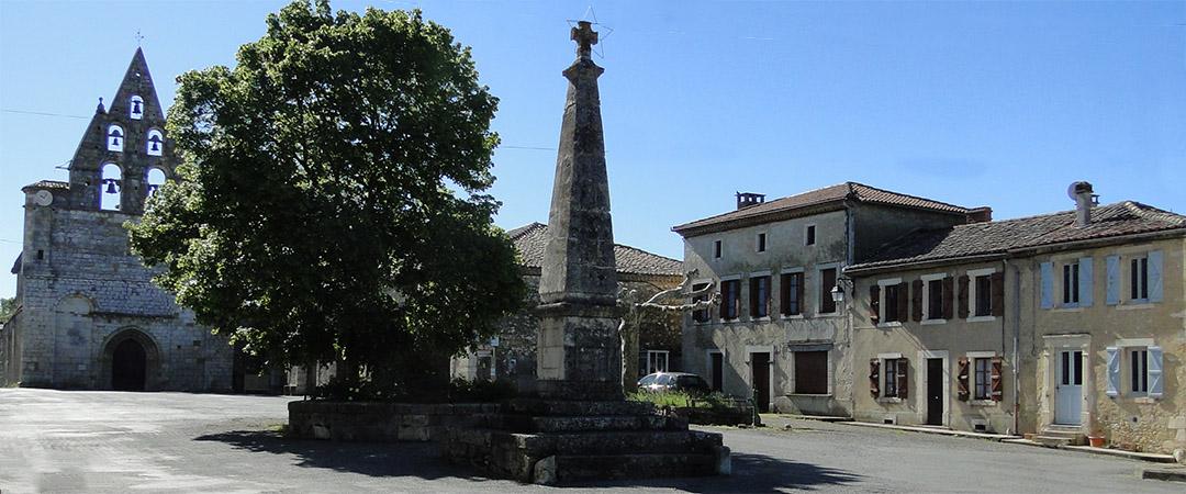 Photo de la place du village avec la pyramide et l'église en fond